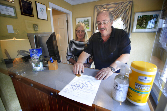 In this Wednesday, June 10, 2020, photo, Cod Cove Inn owners Ted and Jill Hugger show a draft of a compliance form that inn owners may be required to have out-of-state guests sign before being allowed to check in at their inn in Edgecomb, Maine. The form is part of the