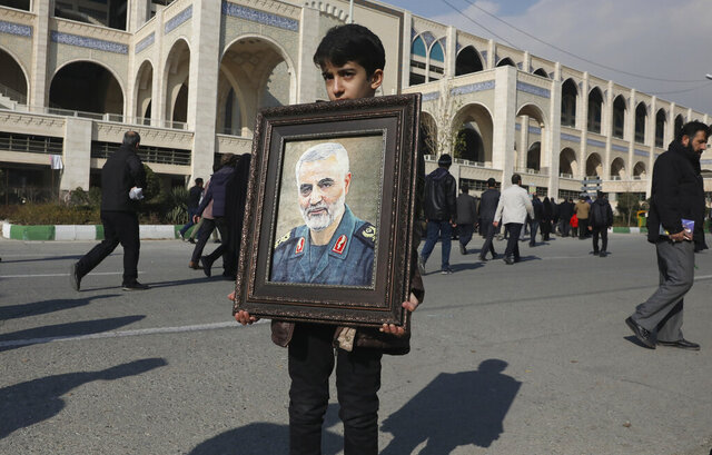 A boy carries a portrait of Iranian Revolutionary Guard Gen. Qassem Soleimani, who was killed in a U.S. airstrike in Iraq, prior to the Friday prayers in Tehran, Iran, Friday Jan. 3, 2020. Iran has vowed