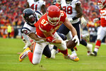 Kansas City Chiefs tight end Travis Kelce (87) scores a touchdown against Houston Texans cornerback Lonnie Johnson Jr. (32) during the first half of an NFL divisional playoff football game, in Kansas City, Mo., Sunday, Jan. 12, 2020. (AP Photo/Ed Zurga)