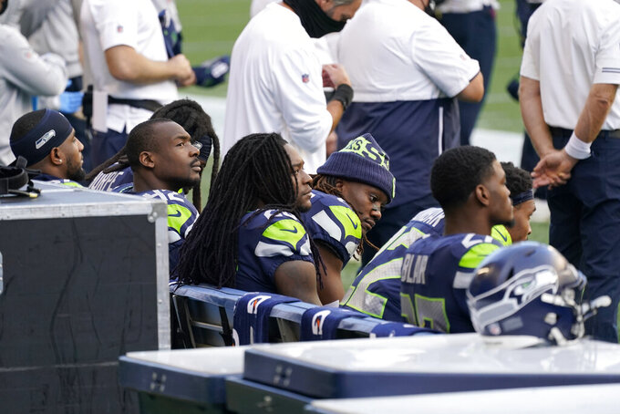 Seattle Seahawks players sit during the playing of the national anthem before an NFL football game against the New England Patriots, Sunday, Sept. 20, 2020, in Seattle. (AP Photo/Elaine Thompson)