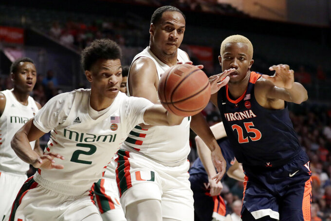 Miami guard Isaiah Wong (2), center Rodney Miller Jr., center, and Virginia forward Mamadi Diakite (25) go for a loose ball during the first half of an NCAA college basketball game, Wednesday, March 4, 2020, in Coral Gables, Fla. (AP Photo/Lynne Sladky)