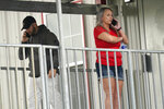 Marion Cuyler, right, fiancée of missing crew member Chaz Morales, and an unidentified man, talk on their phones at a fire station where family members of 12 people missing from a capsized oil industry vessel have been gathering, Thursday, April 15, 2021, in Port Fourchon, La. The lift boat capsized in the Gulf of Mexico during a storm on Tuesday, killing one with 12 others still missing. (AP Photo/Gerald Herbert)