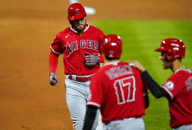 Los Angeles Angels' Shohei Ohtani, front left, and Andrelton Simmons, right, wait to congratulate Jared Walsh as he crosses home plate after hitting a three-run home run off Colorado Rockies relief pitcher Tyler Kinley during the 11th inning of a baseball game Saturday, Sept. 12, 2020, in Denver. The Angels won 5-2. (AP Photo/David Zalubowski)