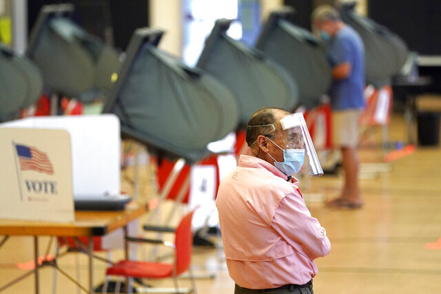 Harris County election clerk Jose Mendoza watches over voting booths, Monday, June 29, 2020, in Houston. Early voting for the Texas primary runoffs began Monday. (AP Photo/David J. Phillip)