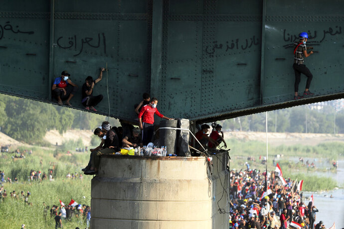 Anti-government protesters try to sneak to the Green Zone while Iraqi security forces close the the Joumhouriya bridge during a demonstration in Baghdad, Iraq, Friday, Nov. 1, 2019. (AP Photo/Hadi Mizban)