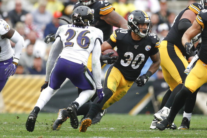 Pittsburgh Steelers running back James Conner (30) runs away from Baltimore Ravens cornerback Maurice Canady (26) during the second half of an NFL football game, Sunday, Oct. 6, 2019, in Pittsburgh. The Ravens won 26-23. (AP Photo/Don Wright)