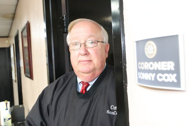 As Greenwood County coroner, Sonny Cox is often one of the first people on the scene when someone dies. Cox, shown here outside his office in Greenwood, S.C., worked for 35 years in law enforcement before first being elected coroner in 2013. (Greg Deal/Index-Journal via AP)