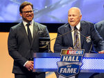 FILE - Hall of Fame inductee Bruton Smith entertains the crowd as his son, Marcus Smith, left, looks on during NASCAR Hall of Fame Induction ceremonies in Charlotte, N.C., in this Saturday, Jan. 23, 2016, file photo. NASCAR wanted new energy and ideas this season and Marcus Smith has been pivotal in helping the sport deliver. The lessons learned from Bruton Smith have helped his son as Marcus Smith takes a bigger role in NASCAR's future planning. (AP Photo/Mike McCarn, File)