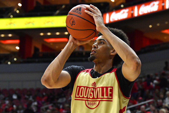 FILE - In this Oct. 12, 2019, file photo, Louisville forward Jordan Nwora warms up before the start of an NCAA college basketball practice in Louisville, Ky. Louisville is back in the national championship conversation after the basketball program was knocked on its heels amid the fallout of embarrassing scandals, including the school's missteps that were discovered in a federal investigation into college basketball and escorts performing in players' dorm. (AP Photo/Timothy D. Easley, File)