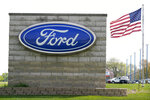 FILE - In this April 27, 2021 file photo, an American flag flies over a Ford auto dealership, in Waukee, Iowa. Ford says it expects 40% of its global sales to be battery-electric vehicles by 2030 as it adds billions to the amount its spending to develop them. Ahead of a presentation to Wall Street on Wednesday morning, May 26 the automaker says it will add about $8 billion to its EV development spending from this year to 2025. (AP Photo/Charlie Neibergall, File)