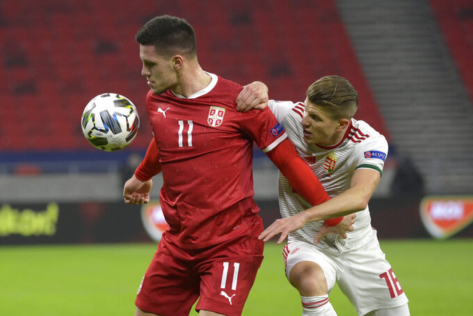 Luka Jovic of Serbia, left, is challenged by David Siger of Hungary for the ball during the UEFA Nations League soccer match Hungary vs. Serbia in Puskas Arena in Budapest, Hungary, Sunday, Nov. 15, 2020. (Szilard Koszticsak/MTI via AP)