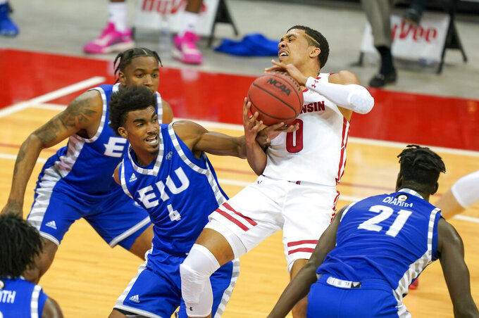 Eastern Illinois' Marvin Johnson (4) fouls Wisconsin's D'Mitrik Trice (0) during the first half of an NCAA college basketball game Wednesday, Nov. 25, 2020, in Madison, Wis. (AP Photo/Andy Manis)