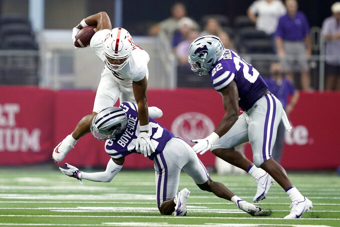 Stanford wide receiver Elijah Higgins (6) is stopped from gaining yardage after a catch as Kansas State defensive back Ekow Boye-Doe (25) and Daniel Green (22) close in during the first half of an NCAA college football game in Arlington, Texas, Saturday, Sept. 4, 2021. (AP Photo/Tony Gutierrez)
