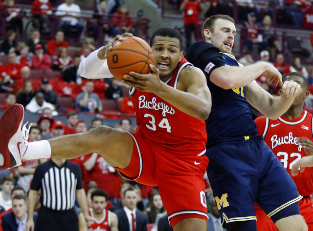 Ohio State forward Kaleb Wesson, left, grabs a rebound against Michigan forward Austin Davis during the first half of an NCAA college basketball game in Columbus, Ohio, Sunday, March 1, 2020. (AP Photo/Paul Vernon)