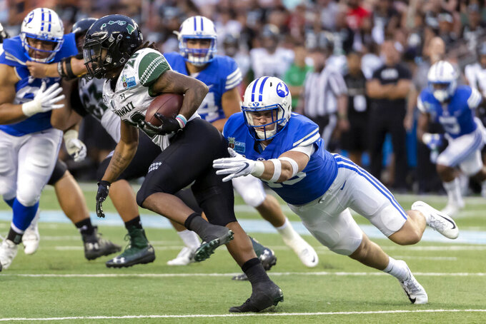 Hawaii running back Miles Reed (26) is tackled from behind by BYU linebacker Payton Wilgar, right, during the second half of the Hawaii Bowl NCAA college football game Tuesday, Dec. 24, 2019, in Honolulu. (AP Photo/Eugene Tanner)