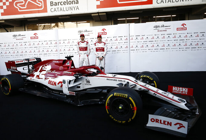 Kimi Raikkonen, right, and Antonio Giovinazzi stand after unveiling the new Alfa Romeo C39 ahead of the Formula One pre-season testing session at the Barcelona Catalunya racetrack in Montmelo, outside Barcelona, Spain, Wednesday, Feb. 19, 2020. (AP Photo/Joan Monfort)
