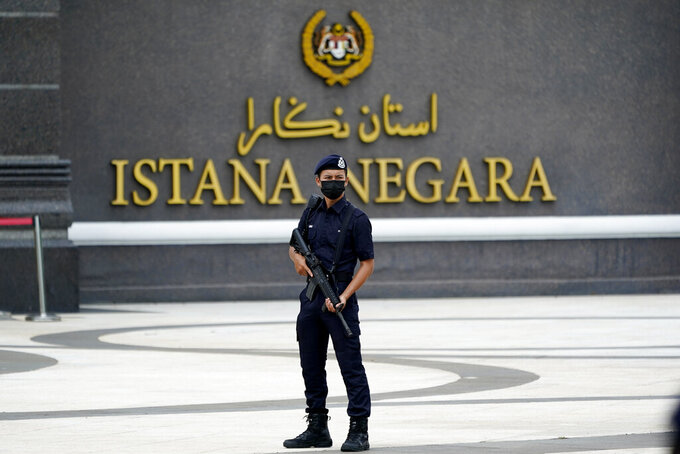 Armed police wearing a face mask to help curb the spread of the coronavirus stands outside National Palace in Kuala Lumpur, Malaysia, Sunday, Oct. 25, 2020. Malay rulers hold a special meeting on Sunday to discuss the government's plan to declare an emergency to tackle the worsening COVID-19 situation. (AP Photo/Vincent Thian)