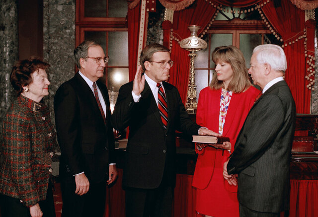 FILE - In this  Tuesday, Dec. 15, 1992 file photo, Sen. Byron Dorgan, D-N.D., re-enacts taking the Senatorial oath from Senate President Pro Tem Robert Byrd of West Virginia, right, as Dorgan's wife Kim holds the bible in Washington. Sen. Jocelyn Burdick, D-N.D., left, and Senate Majority Leader George Mitchell of Maine, second from left, looks on. Jocelyn Burdick, who became the first woman to represent North Dakota in the U.S. Senate when she briefly filled the seat vacated by her late husband, has died, Thursday, Dec. 26, 2019. (AP Photo/John Duricka, File)