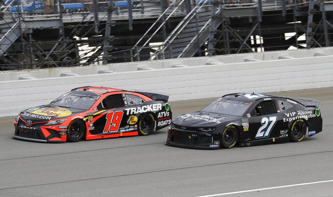 Martin Truex Jr., left, and Reed Sorenson compete during a NASCAR Cup Series auto race at Chicagoland Speedway in Joliet, Ill., Sunday, June 30, 2019. (AP Photo/Nam Y. Huh)