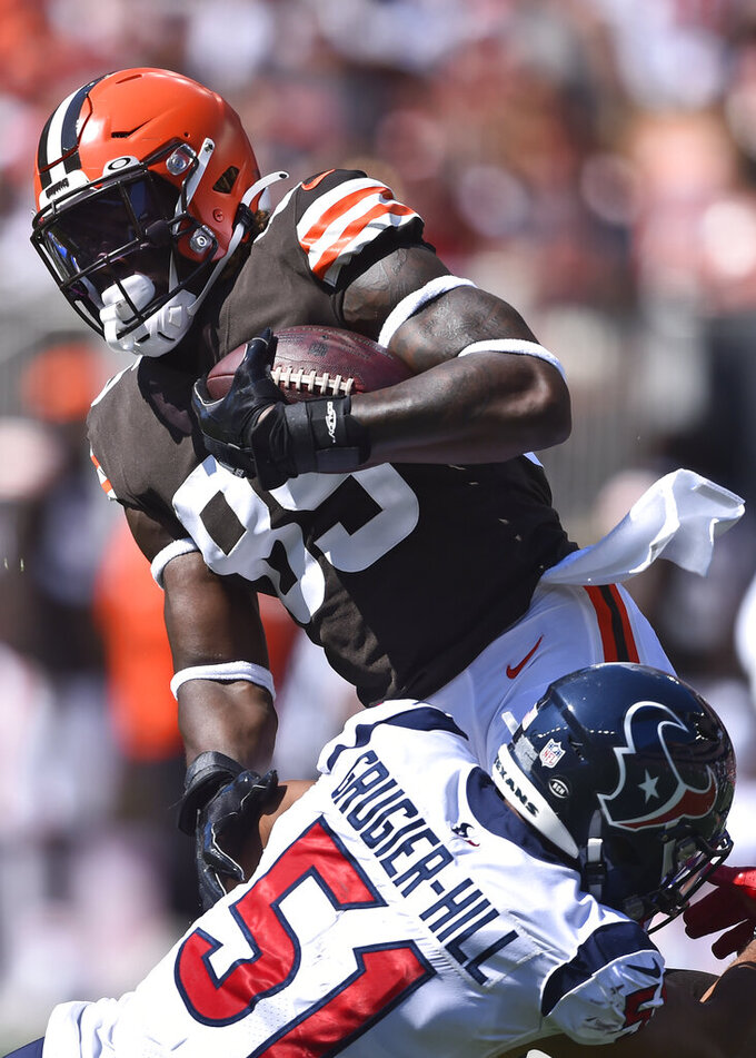 Cleveland Browns tight end David Njoku (85) is stopped by Houston Texans outside linebacker Kamu Grugier-Hill (51) after a catch during the first half of an NFL football game, Sunday, Sept. 19, 2021, in Cleveland. (AP Photo/David Richard)