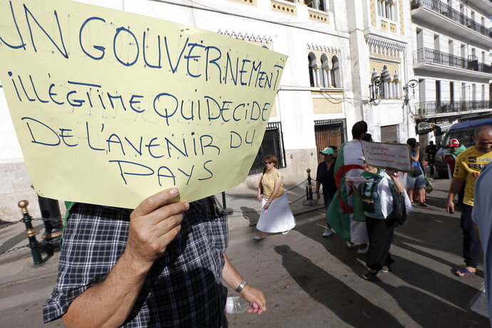 FILE - In this Oct. 18, 2019, file photo, Algerians take part in a protest against the government in Algiers. Algeria's presidential campaign is in trouble. Candidates are struggling to fill rally venues, two campaign chiefs have quit, voters have pelted candidates' headquarters with tomatoes and eggs, and a 9-month-old pro-democracy movement calls the whole thing a sham. Poster reads