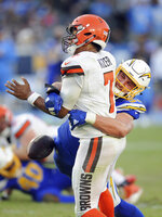 FILE - In this Dec. 3, 2017, file photo, Chargers defense end Joey Boss (99) causes a fumble as he hits Cleveland Browns quarterback DeShone Kizer (7) in the back field during the fourth quarter of an NFL football game in Carson, Calif. Los Angeles is hoping that Bosa will be available when it begins preparations for its Nov. 4 game at Seattle.  Bosa has been out since early in training camp with a foot injury. (AP Photo/John Cordes, File)