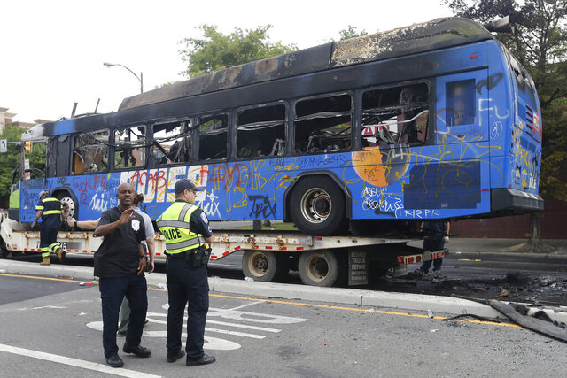 EDS NOTE: OBSCENITY - A burned out Richmond City bus is loaded onto a tow truck after it was burned overnight during demonstrations related to the Minneapolis police actions Saturday May 30, 2020, in Richmond, Va. Protests over the death of George Floyd in Minneapolis police custody have spread to other areas across the United States. (AP Photo/Steve Helber)