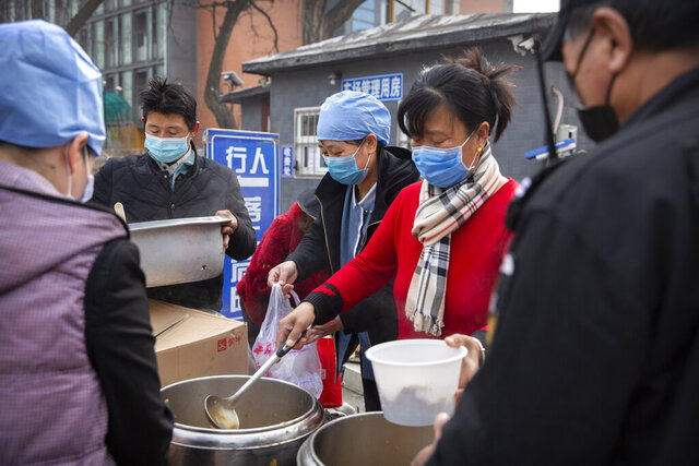Workers in face masks dispense lunch outside of an office building in Beijing, Friday, Feb. 21, 2020. China reported a further fall in new virus cases to 889 on Friday as health officials expressed optimism over containment of the outbreak that has caused more than 2,200 deaths and is spreading elsewhere. (AP Photo/Mark Schiefelbein)