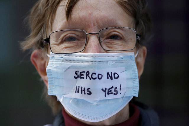 A protester takes part in a demonstration outside the Department of Health and Social Care office in London, over the private company Serco's handling of the British government's coronavirus test, track and trace system, Friday, Sept. 25, 2020. The protesters were on Friday calling for the test, track and trace system to be carried out by local public health teams who work closely with Britain's National Health Service. (AP Photo/Matt Dunham)