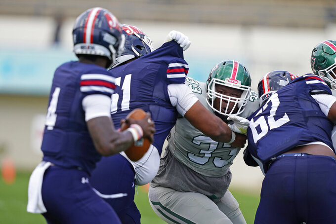 Mississippi Valley State defensive lineman Jeremiah Caine (33) is blocked by two Jackson State offensive linemen including Vincent Sampson (62) during the first half of an NCAA college football game, Sunday, March 14, 2021, in Jackson, Miss. Jackson State won. (AP Photo/Rogelio V. Solis)