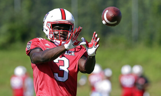 In this photo taken Thursday, Aug. 9, 2018 North Carolina State wide receiver Kelvin Harmon reaches for a pass during an NCAA college football practice in Raleigh, N.C. (AP Photo/Gerry Broome)