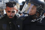 Riot police arrest an injured anti-government protester attempting to prevent the Lebanese lawmakers from reaching the parliament building to attend the 2020 budget discussion session, in downtown Beirut, Lebanon, Monday, Jan. 27, 2020. Lebanese security forces scuffled with protesters near the parliament building,  where lawmakers are scheduled to begin a two-day discussion and later approval of the budget amid a crippling financial crisis. (AP Photo/Hussein Malla)
