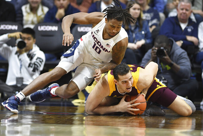 Connecticut's Brendan Adams, left, pressures Iona's Niksa Nikolic in the first half of an NCAA college basketball game, Wednesday, Dec. 4, 2019, in Storrs, Conn. (AP Photo/Jessica Hill)