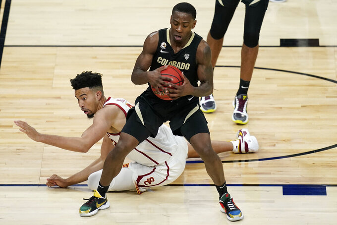 Southern California's Isaiah Mobley, left, tries to steal the ball from Colorado's McKinley Wright IV during the second half of an NCAA college basketball game in the semifinal round of the Pac-12 men's tournament Friday, March 12, 2021, in Las Vegas. (AP Photo/John Locher)