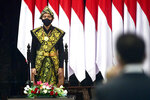 In this photo released by Indonesian Presidential Palace, Indonesian President Joko Widodo, wearing a face mask as a precaution against the new coronavirus outbreak, listens to the national anthem after delivering his national address at the parliament building in Jakarta, Indonesia, Friday, Aug. 14, 2020. Indonesia's president called on all citizens to turn the COVID-19 crisis into an advancement opportunity and pledged health care reforms in an address Friday ahead of the country's 75th anniversary of independence. (Muchlis Jr./Presidential Palace via AP)