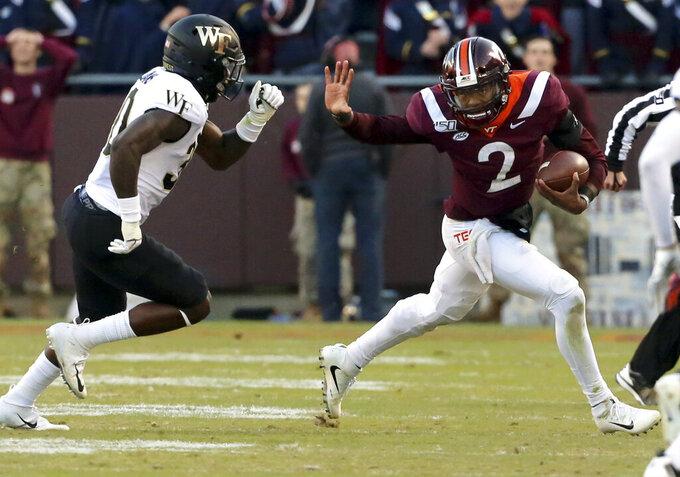 Virginia Tech quarterback Hendon Hooker (2) attempts to elude Wake Forest defender Ja'Cquez Williams (30) during the second quarter of an NCAA college football game Saturday, Nov. 9, 2019, in Blacksburg, Va. (Matt Gentry/The Roanoke Times via AP)
