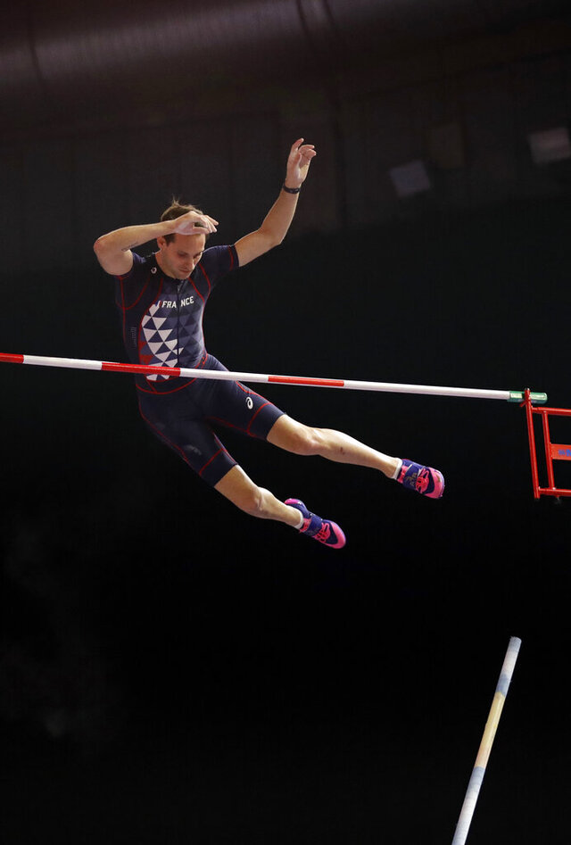 """FILE - In this March 4, 2018, file photo, France's Renaud Lavillenie clears the bar in the men's pole vault final at the World Athletics Indoor Championships in Birmingham, Britain. The three biggest names in men's pole vault will compete against each other from their own backyards, Sunday, May 3, 2020, in a rare sporting event during the coronavirus pandemic. Video links will connect world record holder Mondo Duplantis, world champion Sam Kendricks and former Olympic champion Renaud Lavillenie. World Athletics calls it """"The Ultimate Garden Clash"""" and will stream it on social media.(AP Photo/Matt Dunham, File)"""