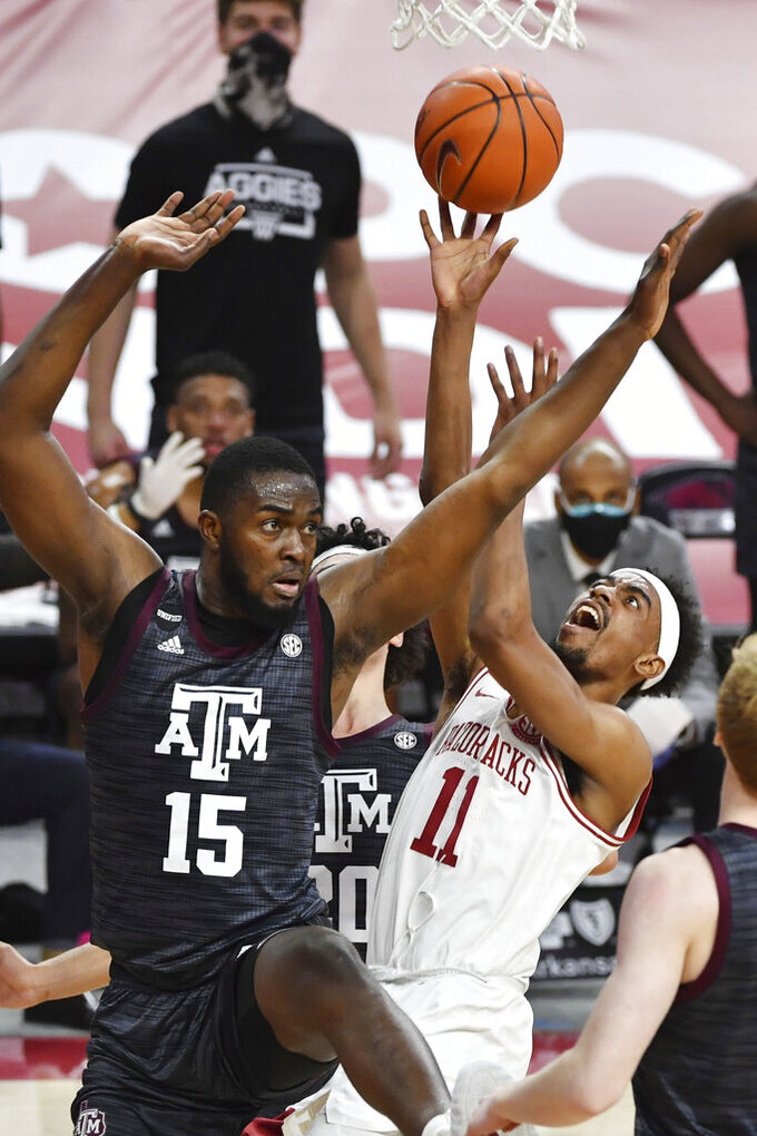 Arkansas guard Jalen Tate (11) is fouled by Texas A&M forward Jonathan Aku (15) as he drives to the hoop during the first half of an NCAA college basketball game in Fayetteville, Ark., Saturday, March 6, 2021. (AP Photo/Michael Woods)