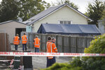 Workers walk outside a crime scene tent at Linwood mosque in Christchurch, New Zealand, Thursday, March 21, 2019. Police officials in New Zealand say the man responsible for killing 50 people at two mosques was on his way to a third attack when police arrested him.  (AP Photo/Vincent Thian)