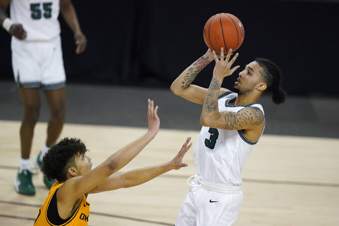 Cleveland State's Craig Beaudion (3) shoots over Oakland's Trey Townsend (13) during the second half of an NCAA college basketball game in the men's Horizon League conference tournament championship game, Tuesday, March 9, 2021, in Indianapolis. (AP Photo/Darron Cummings)