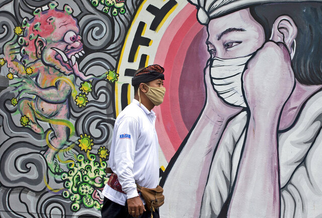 A man walks past a coronavirus-themed mural in Denpasar, Bali, Indonesia, Tuesday, Jan. 26, 2021. Indonesia has reported more cases of the virus than any other countries in Southeast Asia. (AP Photo/Firdia Lisnawati)