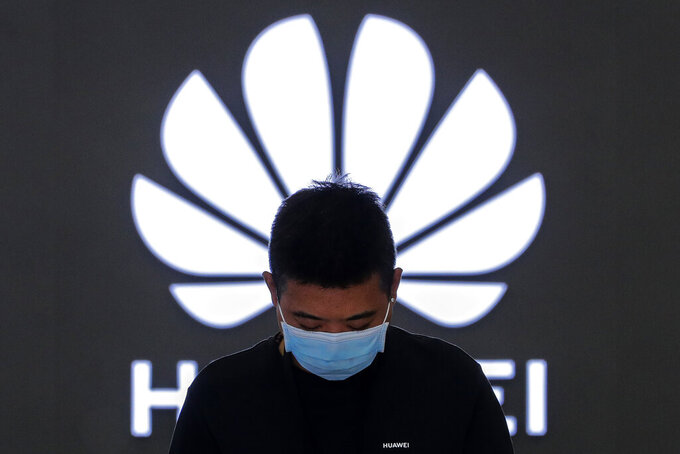 FILE - In this Aug. 31, 2020, file photo, an employee wearing a face mask to help curb the spread of the coronavirus stands inside a Huawei flagship store in Beijing.  Chinese tech giant Huawei said Wednesday, March 31, 2021, it eked out a gain in sales and profit last year but growth plunged after its smartphone unit was hammered by U.S. sanctions imposed in a fight with Beijing over technology and security.(AP Photo/Andy Wong, File)