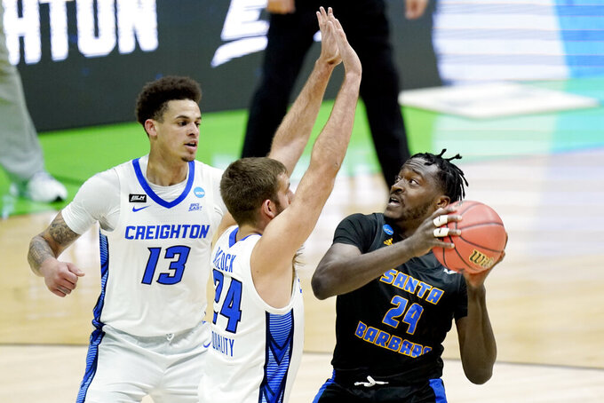 UC Santa Barbara's Robinson Idehen, right, is defended by Creighton's Mitch Ballock, center, and Christian Bishop (13) during the first half of a college basketball game in the first round of the NCAA tournament at Lucas Oil Stadium in Indianapolis Saturday, March 20, 2021. (AP Photo/Mark Humphrey)