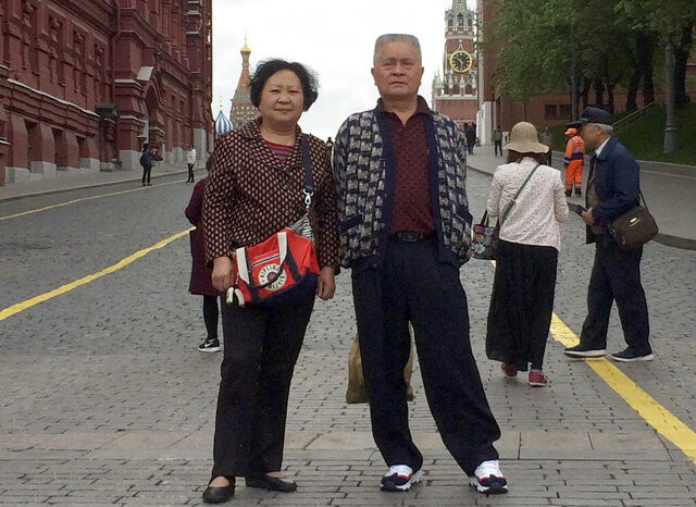 This May 13, 2019 photo provided by Liu Dong'e shows her and her husband, Wu Chuanyong, while visiting Moscow. Wu Chuanyong had been enjoying a peaceful retirement in the central Chinese city of Wuhan. The 68-year-old family patriarch began each morning with a stroll through the park and ended the day watching television dramas. Then the coronavirus hit, quickly spreading in Wuhan and around the world. (Courtesy Liu Dong'e via AP)
