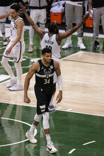Milwaukee Bucks forward Giannis Antetokounmpo (34) walks away after scoring and being fouled by Brooklyn Nets' James Harden during the second half of Game 6 of a second-round NBA basketball playoff series Thursday, June 17, 2021, in Milwaukee. (AP Photo/Jeffrey Phelps)