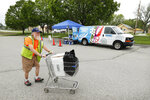 Lewis Claussen pushes his cart after picking up food at a Des Moines Area Religious Council Food Pantry stop, Wednesday, May 20, 2020, in Des Moines, Iowa. As food banks have struggled to meet soaring demand from people suddenly out of work because of the coronavirus outbreak, it has been especially troubling to see farmers have to bury produce, dump milk and euthanize hogs. Now some states are spending more money to help pay for food that might otherwise go to waste, the U.S. Agriculture Department is spending $3 billion to help get farm products to food banks, and a senator is seeking $8 billion more to buy farm produce for food banks. (AP Photo/Charlie Neibergall)