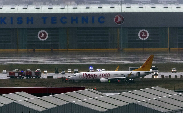 Members of emergency services work around a passenger plane that skidded off the runway at the Sabiha Gokcen Airport in Istanbul, Tuesday, Jan. 7, 2020, temporarily shutting down the airport. The Boeing 737-800 from Sharjah, United Arab Emirates, operated by Turkish low-cost airline Pegasus, skidded as it landed in the morning and Istanbul governor's office said all 164 passengers were safely evacuated by emergency slides Storms and heavy rain have affected the city and transportation since Sunday night. (IHA via AP)