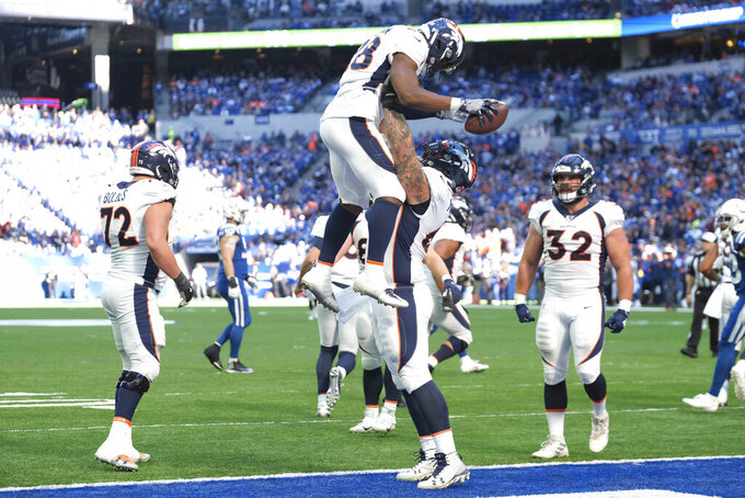 Denver Broncos' Royce Freeman (28) celebrates scoring a touchdown with Connor McGovern (60) during the second half of an NFL football game against the Indianapolis Colts, Sunday, Oct. 27, 2019, in Indianapolis. (AP Photo/AJ Mast)