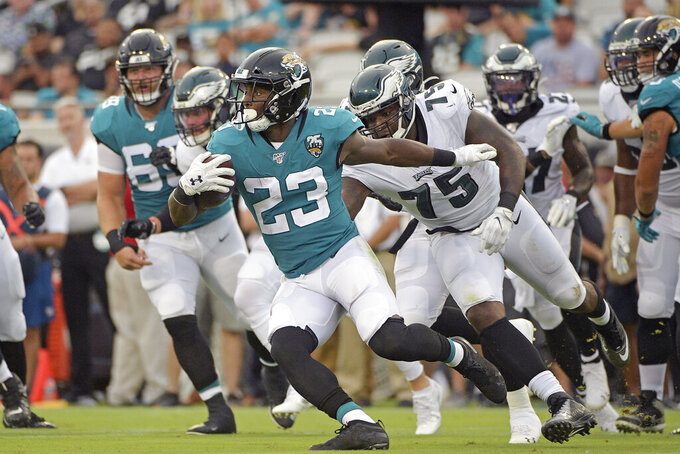Jacksonville Jaguars running back Alfred Blue (23) runs past Philadelphia Eagles defensive end Vinny Curry (75) for yardage during the first half of an NFL preseason football game, Thursday, Aug. 15, 2019, in Jacksonville, Fla. (AP Photo/Phelan M. Ebenhack)