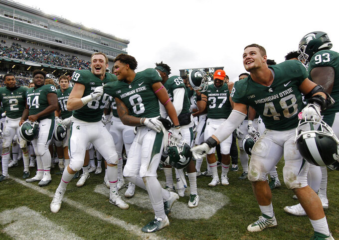 Michigan State players, including Matt Dotson (89), Jalen Nailor (8) and Kenny Willekes (48), celebrate following a 23-13 win over Purdue in an NCAA college football game, Saturday, Oct. 27, 2018, in East Lansing, Mich. (AP Photo/Al Goldis)